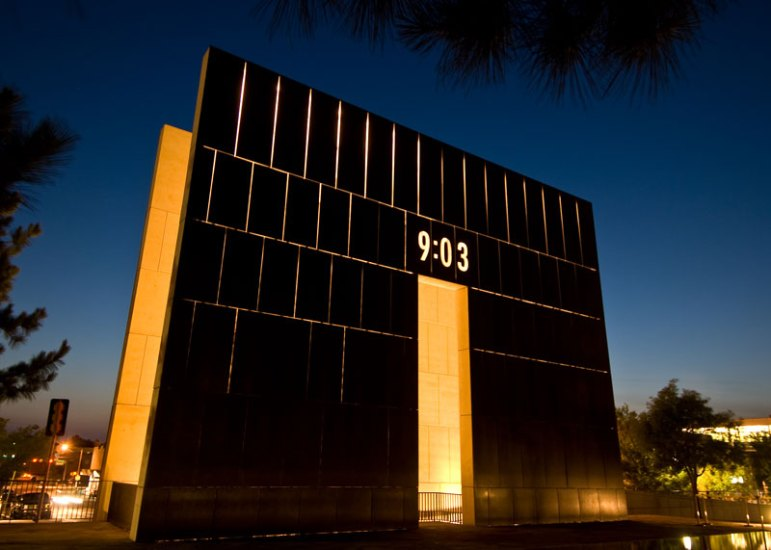 Twin portals bracket the moment of destruction. The East Gate, marks the time of the morning on April 19, 1995, and represents the innocence of the city before the attack. The West Gate reads 9:03, the minute after the blast. Image courtesy Oklahoma City National Memorial.