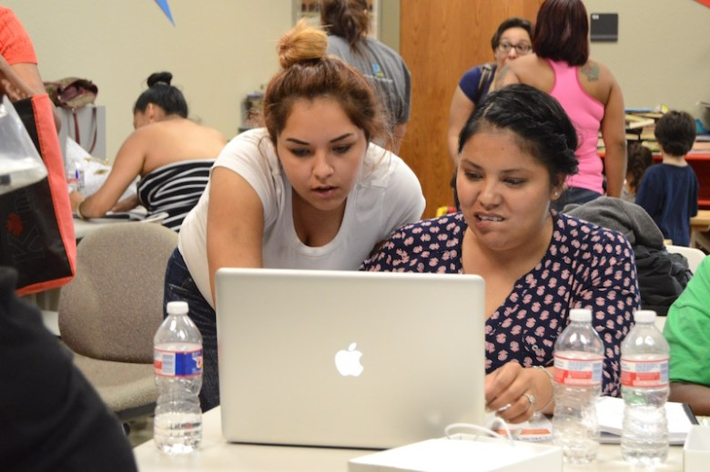 MacBook Academy student Adriana Buentello helps fellow student Maria Garcia  (right) with the final test for the course. Photo by Lea Thompson