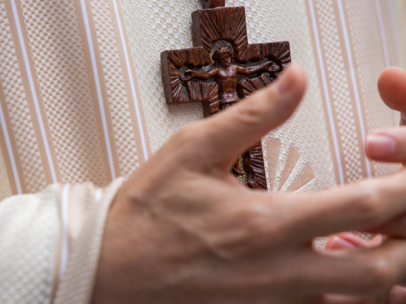Archbishop Gustavo García-Sille holds his hands in front of the cross during a conversation. Photo by Scott Ball.