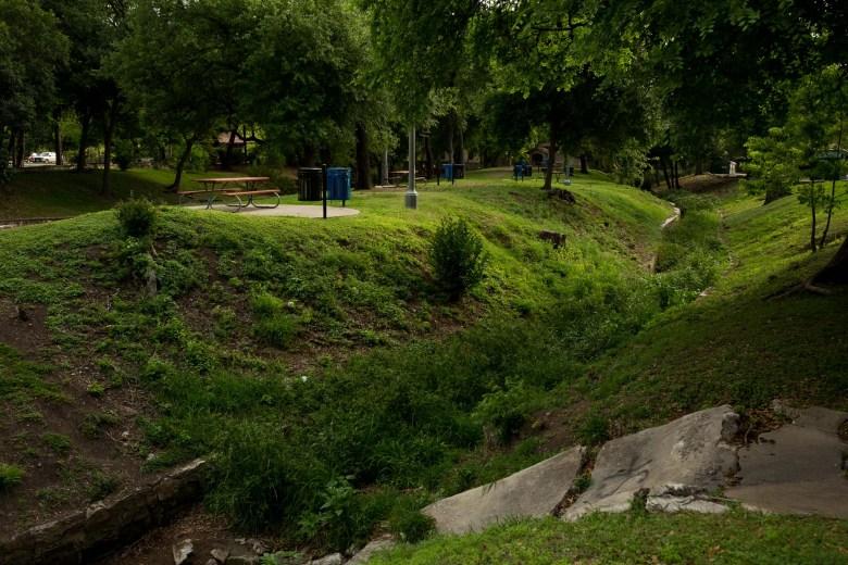 The dried up acequia weaves through picnic areas at Brackenridge Park. Photo by Scott Ball.