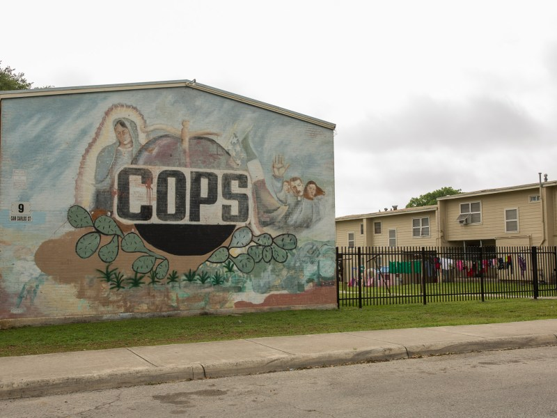 A mural of COPS is displayed on the side of a housing building at Cassiano Homes. Photo by Scott Ball.