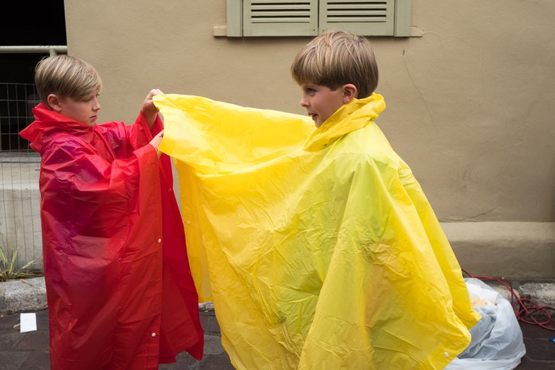 Cebel, 10, helps his friend Wells put on his poncho. Photo by Scott Ball.