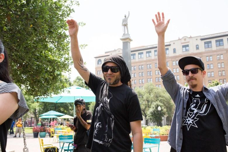 Local artists Nic Soupé and Shek Vega raise their hands. Photo by Scott Ball.