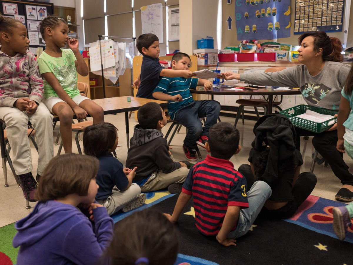 Kindergarten teacher Ms. Ibarra collects reading and writing assignments from students. Photo by Scott Ball.