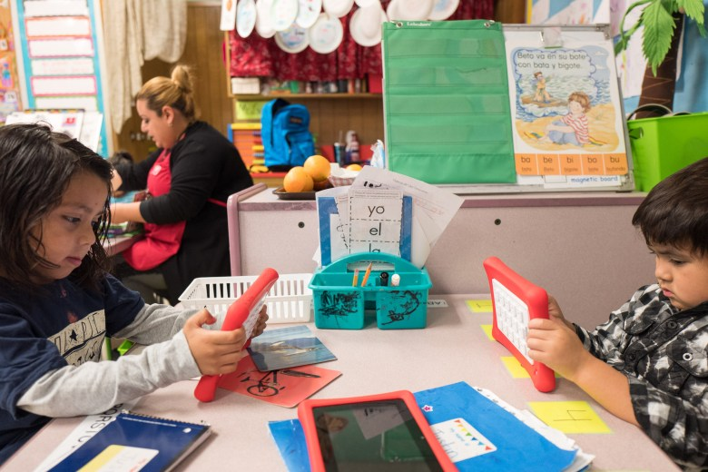 Bilingual Pre-K students Justin and Selvin do reading and language exercises on tablets. Photo by Scott Ball.