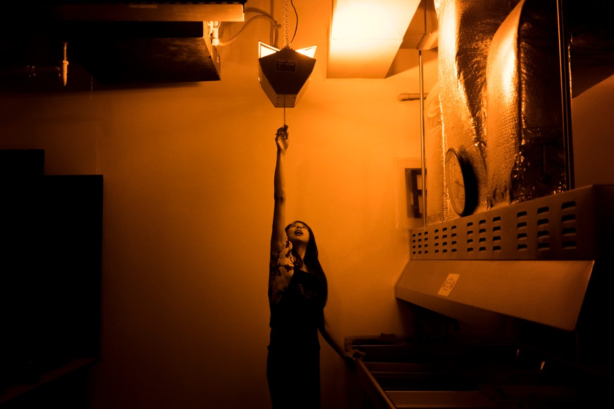 SSA BFA student Lauri Garcia Jones reaches up to turn on the light in the darkroom where she is developing photos for her exhibit. Photo by Kathryn Boyd-Batstone