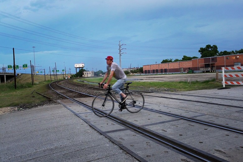 One of the SATX Social Riders crosses the East Side train tracks, part of the 11.5 mile course. Photo by Kathryn Boyd-Batstone