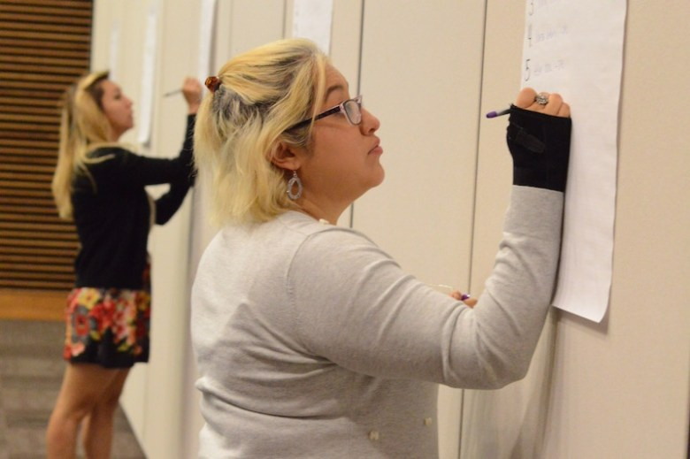 Christina Fitzgerald, an employee of the City's Early Head Start Program, signs up for small group discussions during the hunger summit. Photo by Lea Thompson