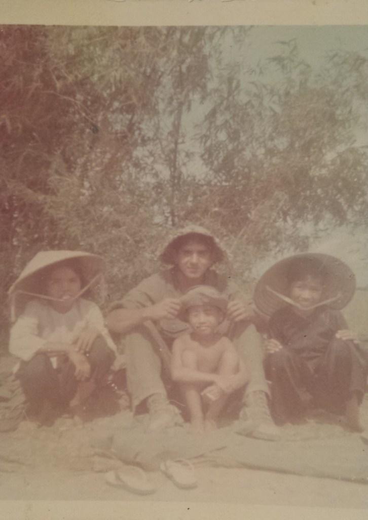 Sgt. Fernando Herrera with three Vietnamese children, circa 1968. Photo courtesy of Sgt. Fernando Herrera.