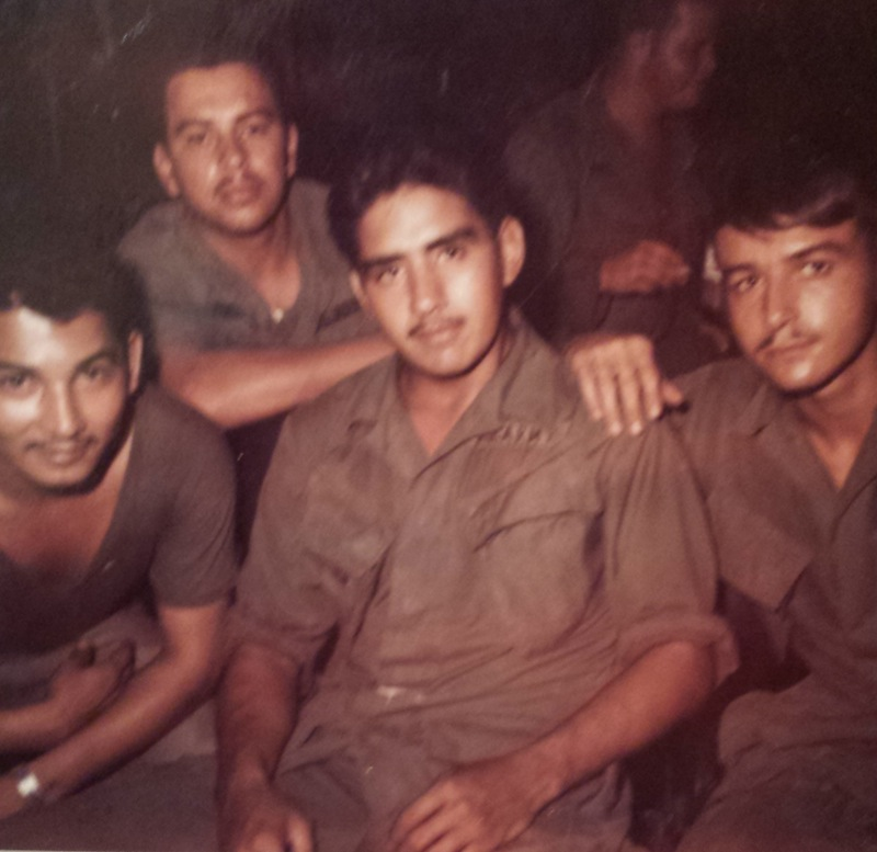 """Sgt. Fernando Herrera (center), Sgt """"Killer"""" Kaiser (right), and two fellow soldiers take a moment to relax at night in Vietnam. """"Tunnel rats"""" like Kaiser were slightly-built soldiers who crawled through North Vietnamese tunnels fighting North Vietnamese soldiers and Vietcong. After the Vietnam Conflict ended, it was discovered that Cu Chi had the highest number of tunnels in Vietnam, and the site included a hospital. Cu Chi, Vietnam, circa 1968."""