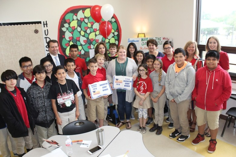 Hawthorne Academy teacher Roberta Moglia holds a sign with her students after receiving the $5,000 grant for a new program to bring Shakespeare plays for students. Standing in the back is Superintendent Pedro Martinez and Hawthorne Principal Pita Rodriguez. Photo courtesy of SAISD.