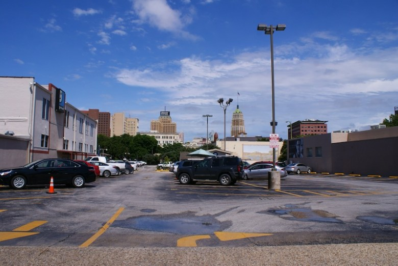 Instead of this empty parking lot, the proposed pedestrian paseo would create a more inviting space for people to congregate. Photo by Alex Barrera.