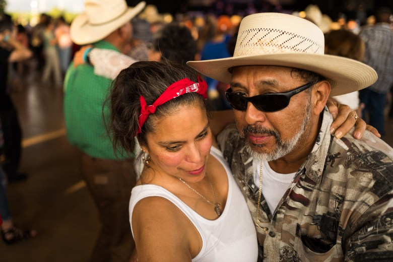 A couple dances close together as they sway and spin through circles of crowds. Photo by Scott Ball.
