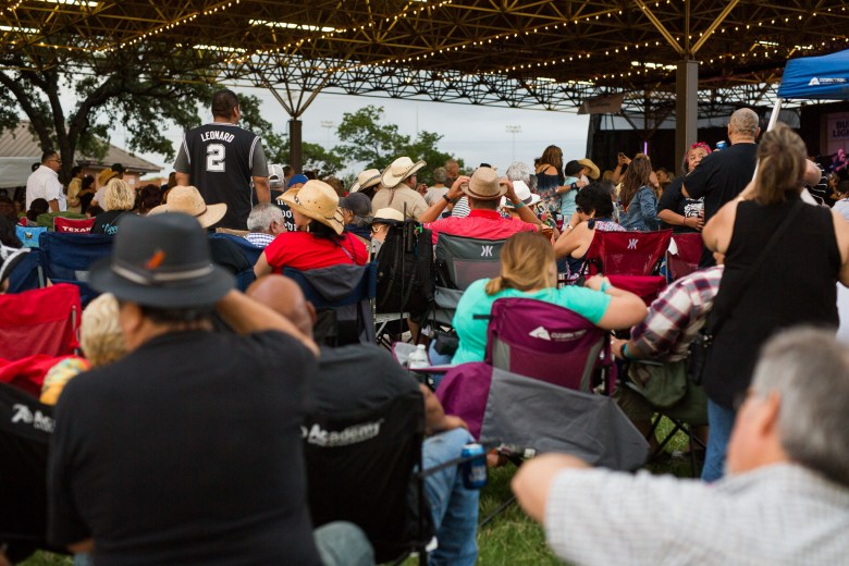 Hundreds of festival attendees sit in chairs brought from home to enjoy the cultural music. Photo by Scott Ball.