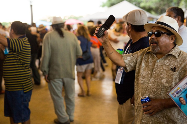 A festival attendee holds up his phone as a band plays nearby. Photo by Scott Ball.