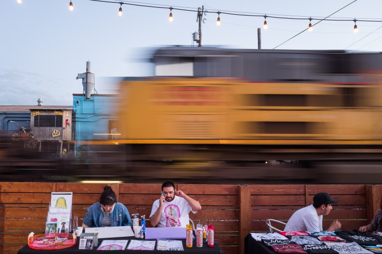 Art vendors such as Broseph's Goods display their work as a train passes by. Photo by Scott Ball.