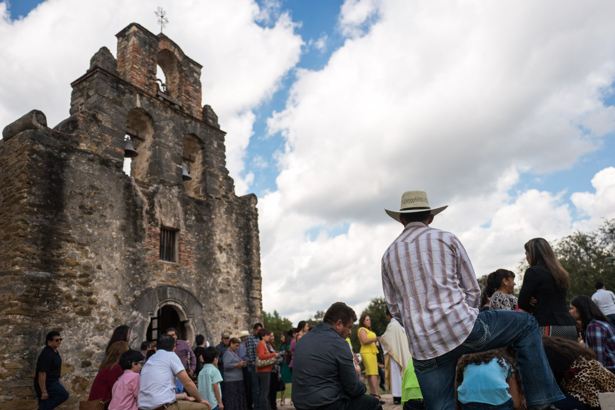 Community members congregate outside of Mission San Francisco de la Espada following a church service on Sunday. Photo by Scott Ball.