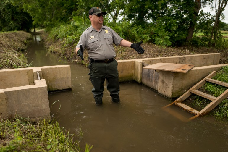 National Park Services educator Tom Castanos stands in the San Juan Acequia as he demonstrates how the National Park Service controls the flow of water. Photo by Scott Ball.