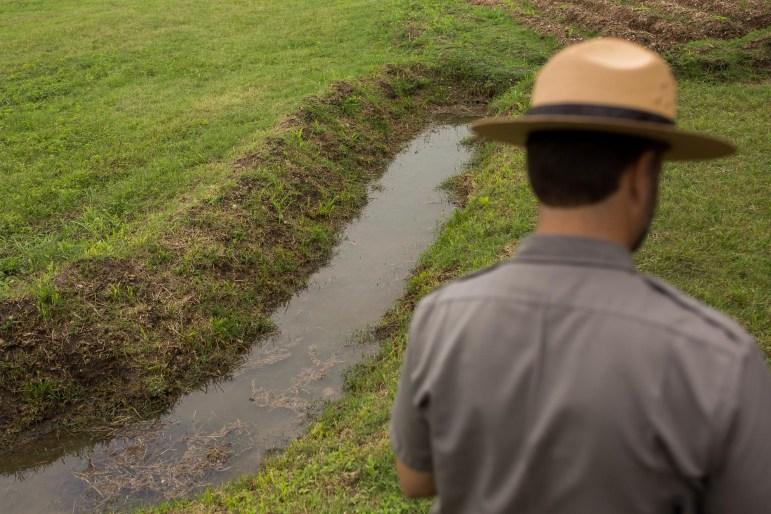 A National Park Service employee walks along a portion of the San Juan Acequia. Photo by Scott Ball.