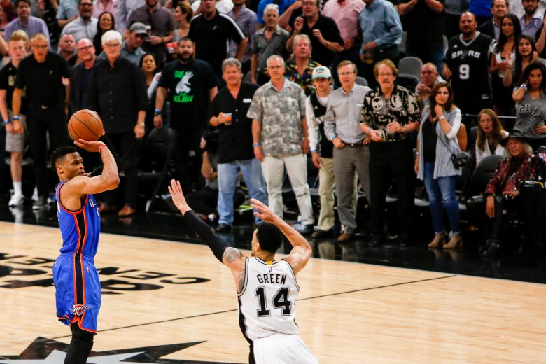 Thunder Guard #0 Russell Westbrook shoots a three over Spurs Guard #14 Danny Green. Photo by Scott Ball.