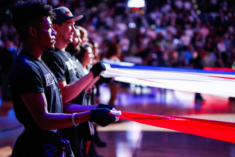 Members of Team Energy hold the American Flag during the National Anthem. Photo by Scott Ball.