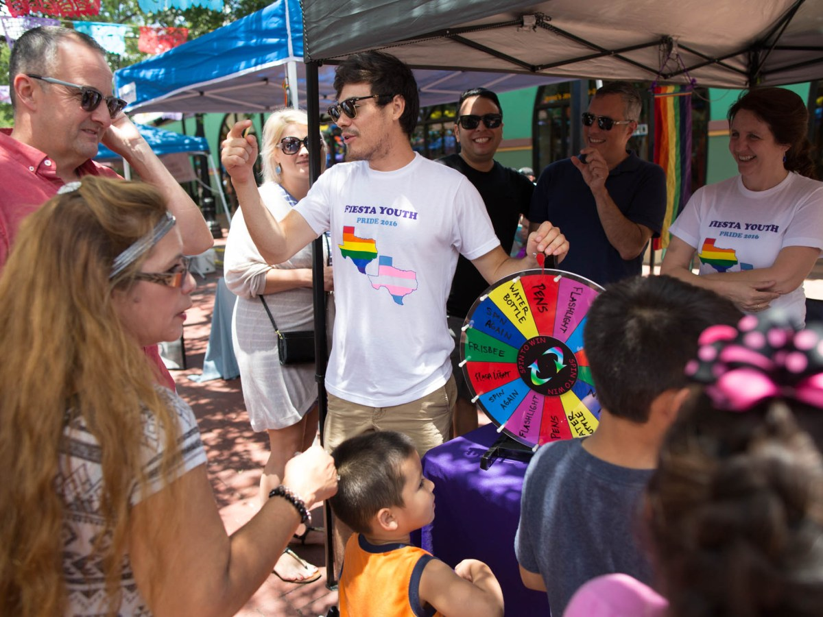 Fiesta Youth Volunteers invite people to play a game at their booth during the Family Pride Fair. Photo by Michael Cirlos.