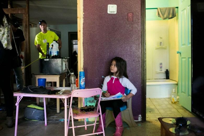 Jennifer Miller's daughter Scarlett looks on as H-E-B workers restore her house. Photo by Kathryn Boyd-Batstone.
