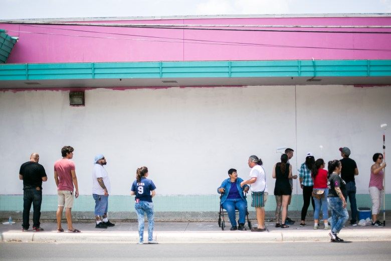 Mary Agnes works with UTSA students to prime the wall outside of Guadalupe Cultural Arts Center and Family Dollar for San Antonio Cultural Art Center's 50th mural. Photo by Kathryn Boyd-Batstone.