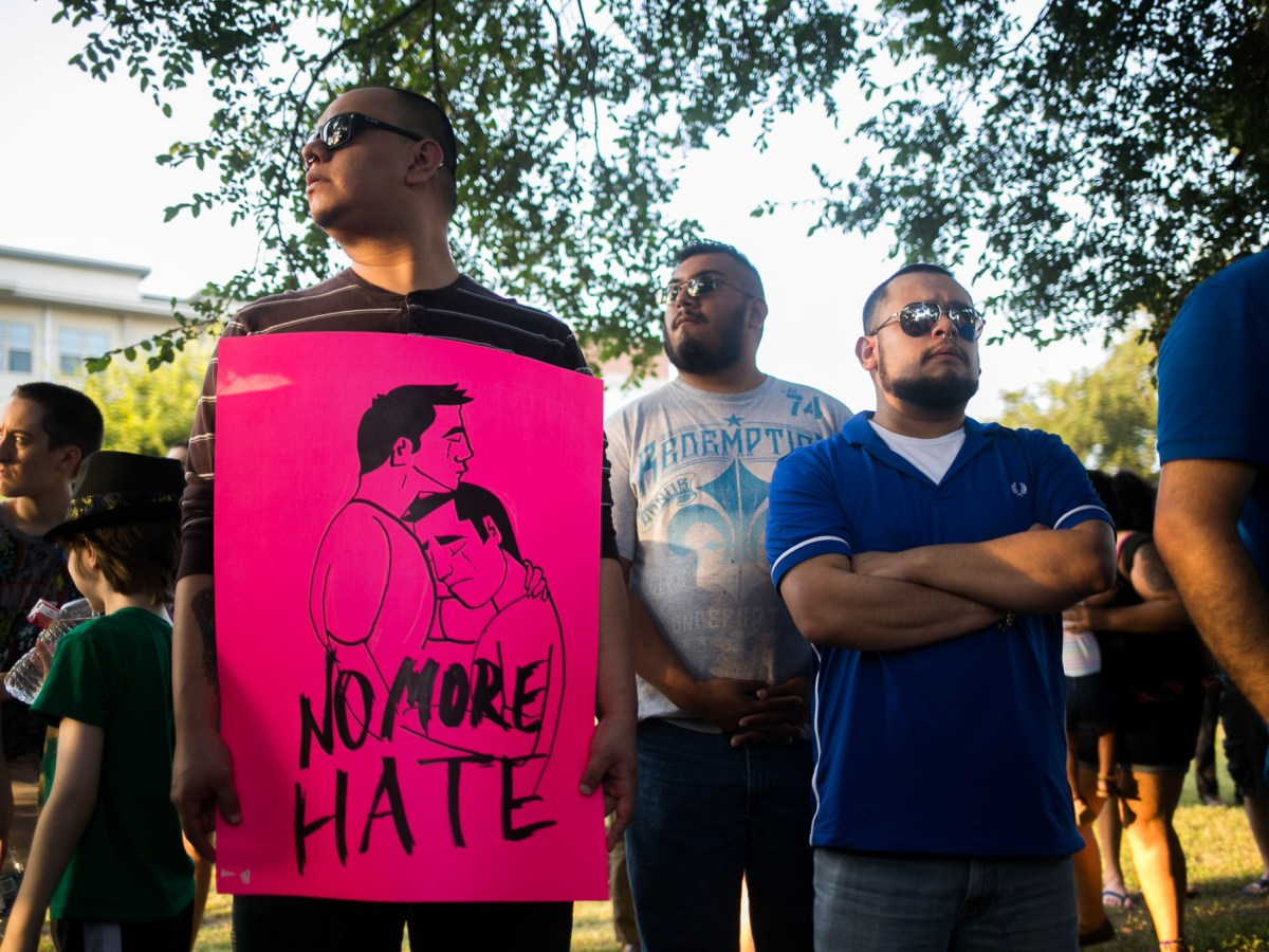 Aldo Martinez holds a sign he drew calling for the end of hate. Photo by Kathryn Boyd-Batstone.