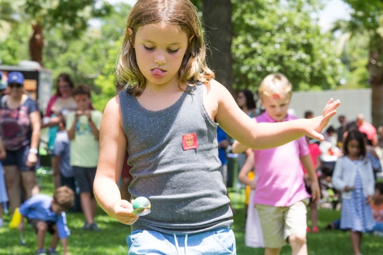 Children race across The McNay's lawn while balancing eggs on spoons during Director William J. Chiego's 25-year celebration event. Photo by Michael Cirlos.