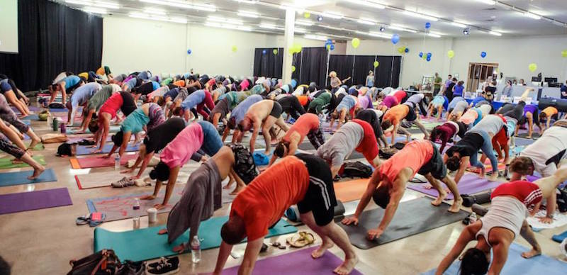 More than 100 yogis practice downward facing dog at a Yoga Day event at TriPoint Event Center in May 2015. Photo by Stacey Anne Photography.