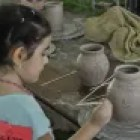 A young girl building a pottery piece. Photo courtesy of the Texas Folklife Festival.