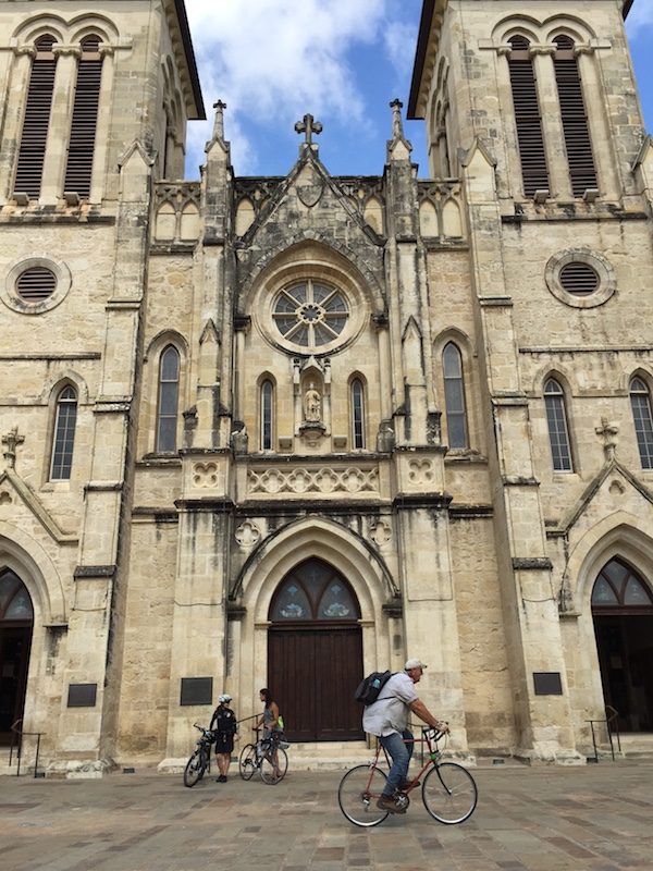 Elena Studier met with local biking advocates at San Fernando Cathedral during her jaunt through San Antonio. Photo by Robert Rivard.