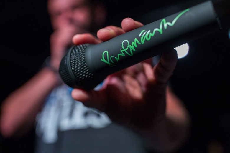 Christian Torres holds up the Paul McCartney signed microphone before the auction begins. Photo by Scott Ball.