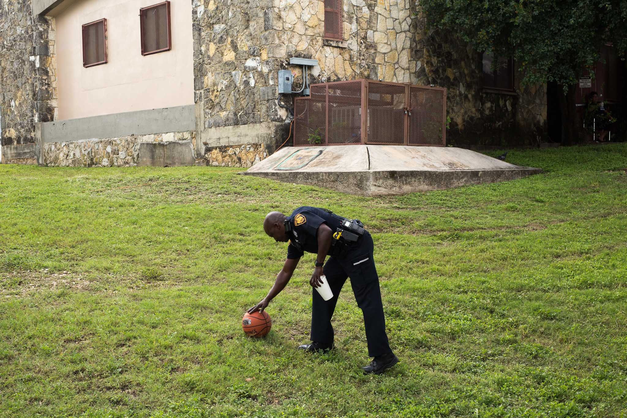 A San Antonio Police Department Officer picks up a loose basketball. Photo by Scott Ball.