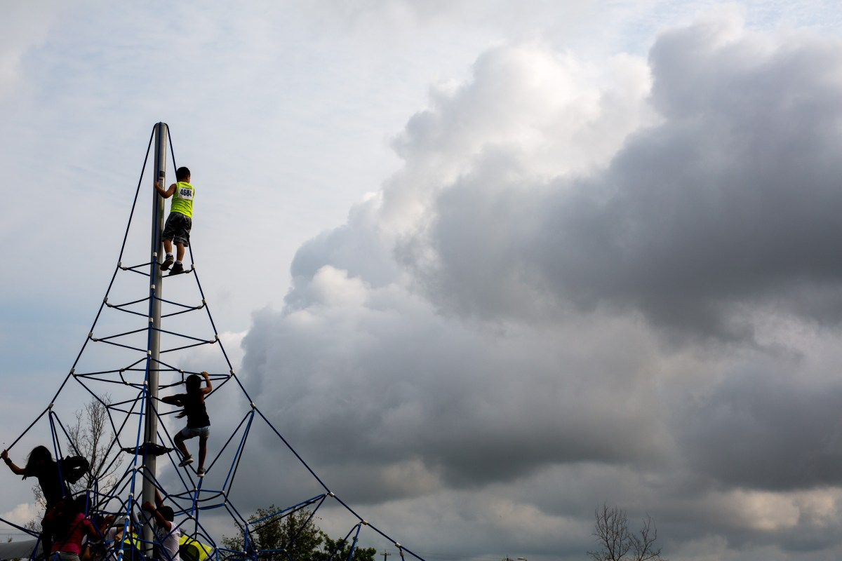 Children climb to the highest point of the newly installed playground. Photo by Scott Ball.