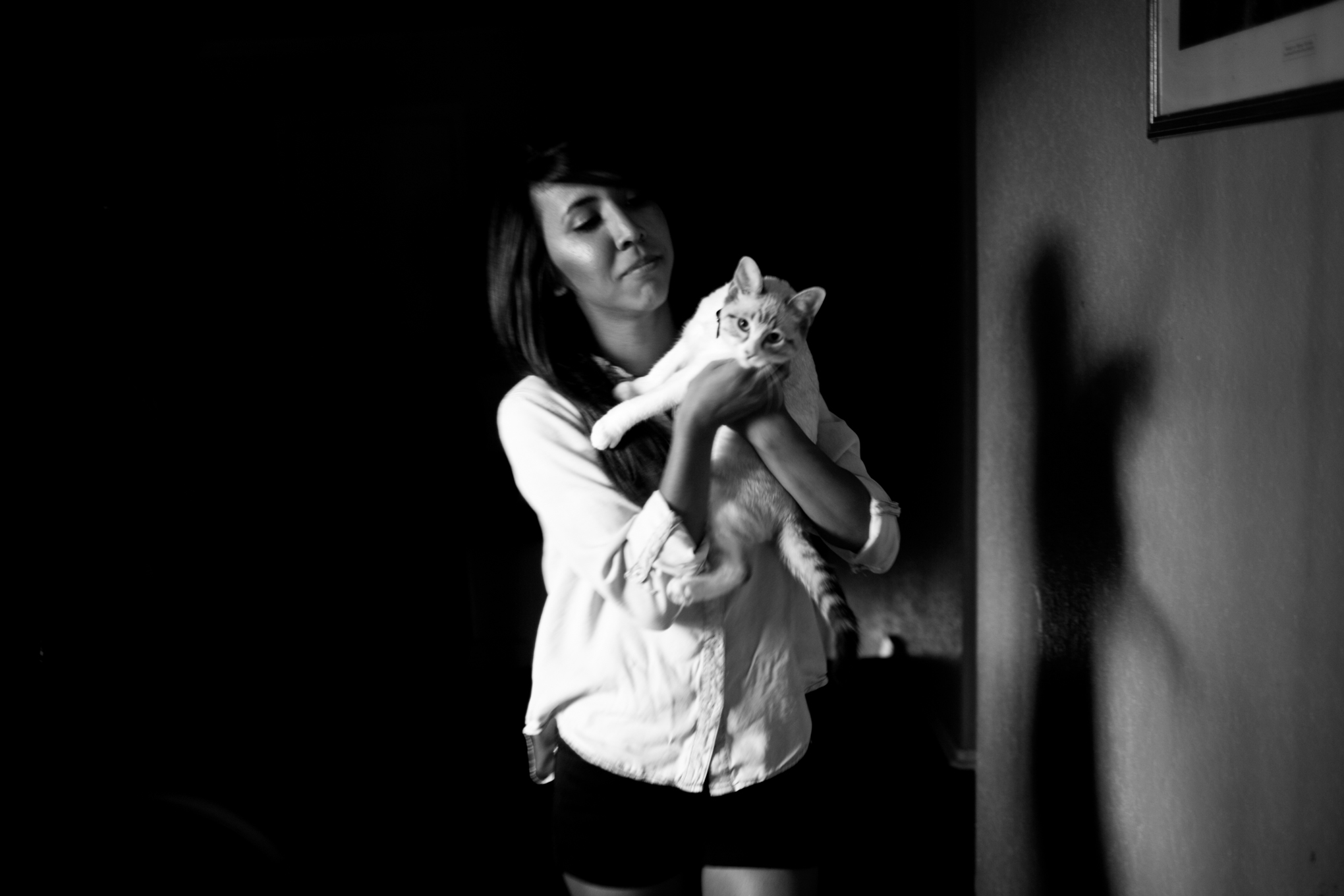 Araceli plays with her cat Cloud. Through all the moves her cat has stayed with her. Photo by Kathryn Boyd-Batstone.