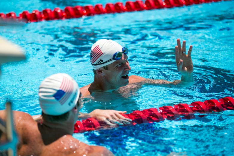 Olympic gold medalist and former world record-holder Josh Davis asks for his time after a practice relay with Olympic swimmer and UT grad Jimmy Feigen. Photo by Kathryn Boyd-Batstone.
