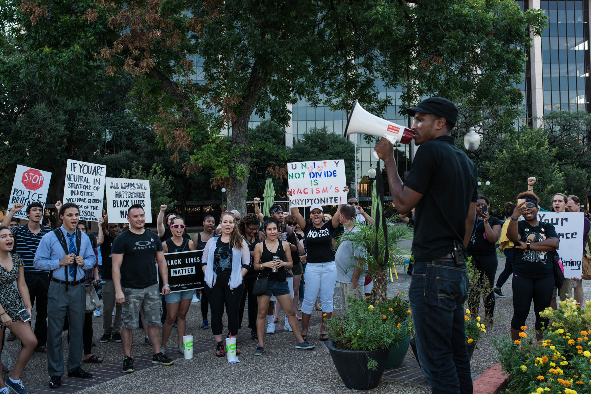 Johnathan Jones, 24, leads the crowd in a chant during his closing remarks as he and other community members took time to speak. Photo by Anthony Francis.