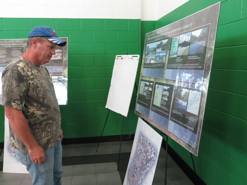 Brady Alexander looks at renderings of the Brackenridge Park Master Plan. Photo by Rocio Guenther