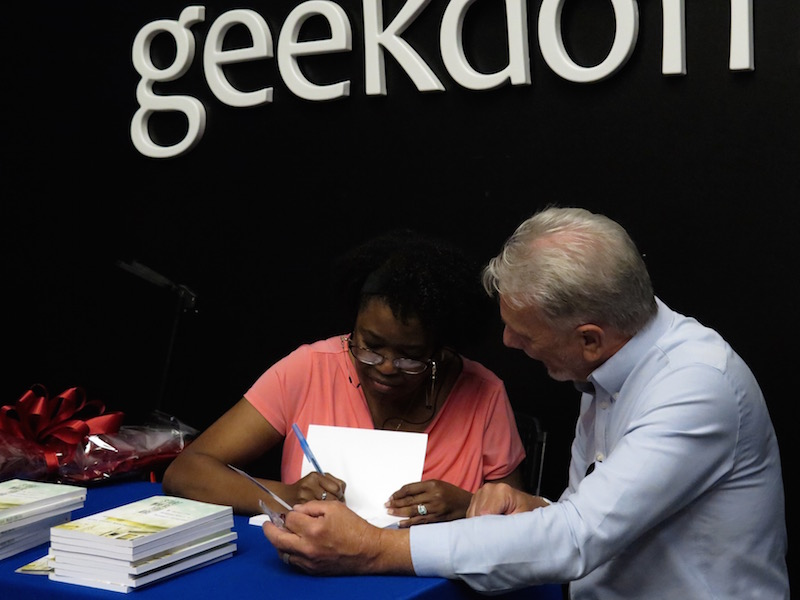 Myra Evans-Manyweather signs a copy of her book for an attendee of her release party Tuesday at the Geekdom Event Centre. Photo by Sarah Sarah Talaat.