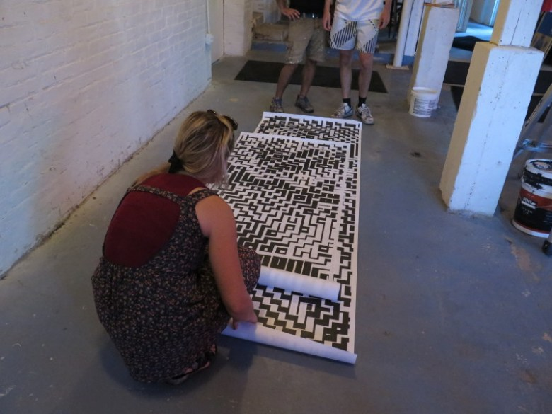 Lex lays out the paper that will be used to make the wall art outside of Burleson Yard. Photo by Rocío Guenther.