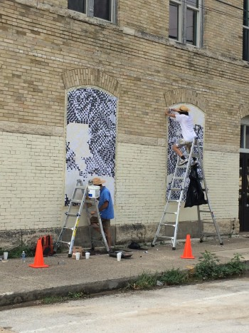 Artist duo Sten Lex use glue and paper to make their mural. Photo courtesy of Luminaria.