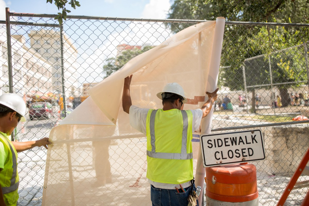 Construction workers strap large fence shades that read 'Reimagine The Alamo' around a worksite. Photo by Scott Ball.