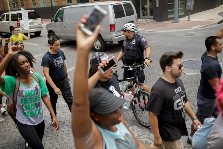 San Antonio Police officers escort the protesters through downtown. Photo by Scott Ball.