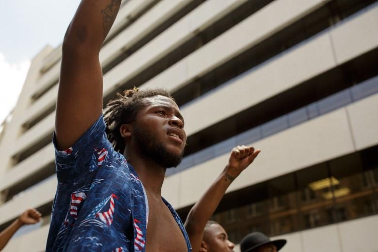 "Malik White raises his fist while shouting, ""Shut it down."" Photo by Scott Ball."