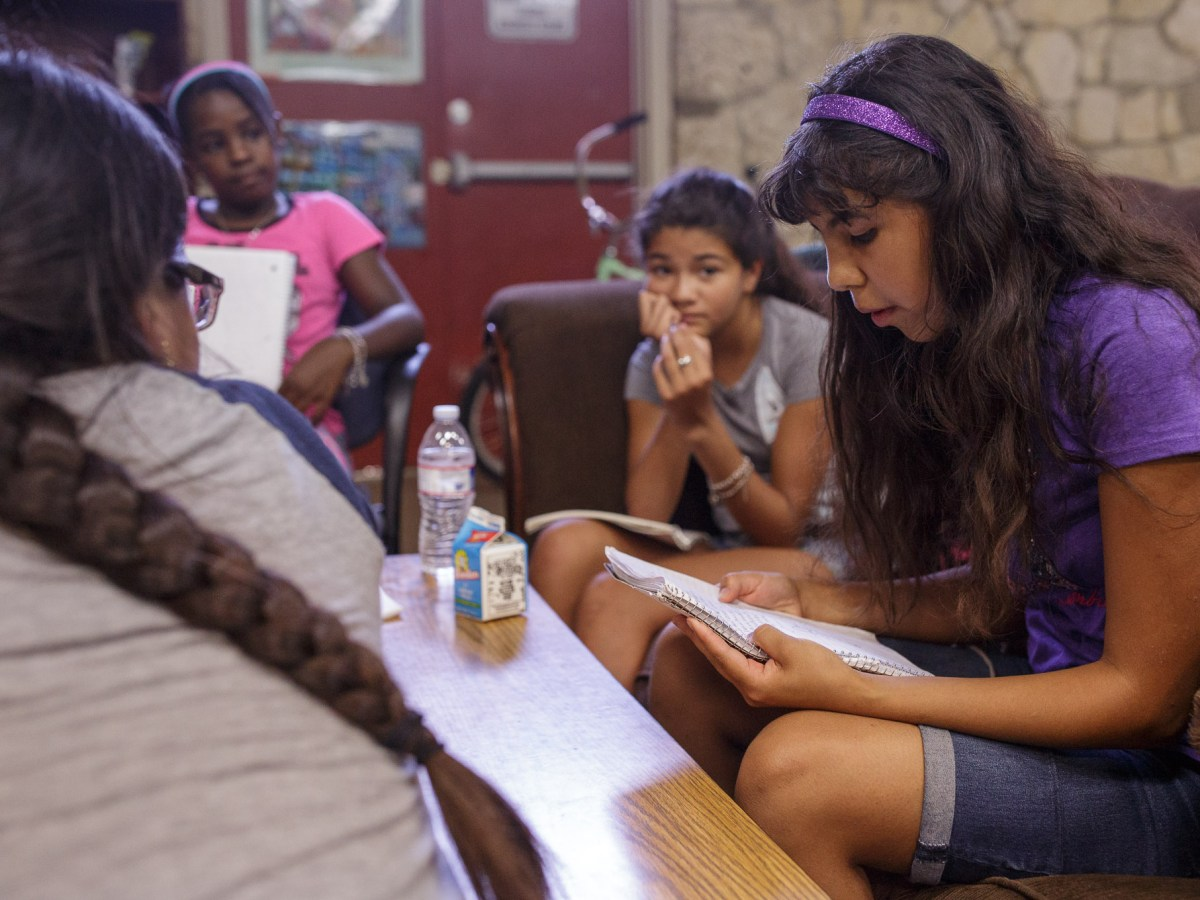 Evelyn, 12, reads a poem she recently completed. Photo by Scott Ball.