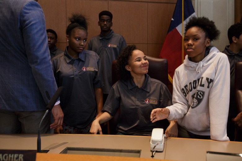 Eastside Dreamers sit in the chairs of council members and Mayor Taylor at City Council chambers. Photo by Scott Ball.