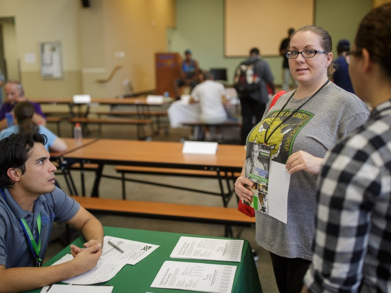 Tara McClenic looks at her daughter Alexia, 17, as she talks with a vendor at the Haven for Hope resources fair. Photo by Scott Ball.