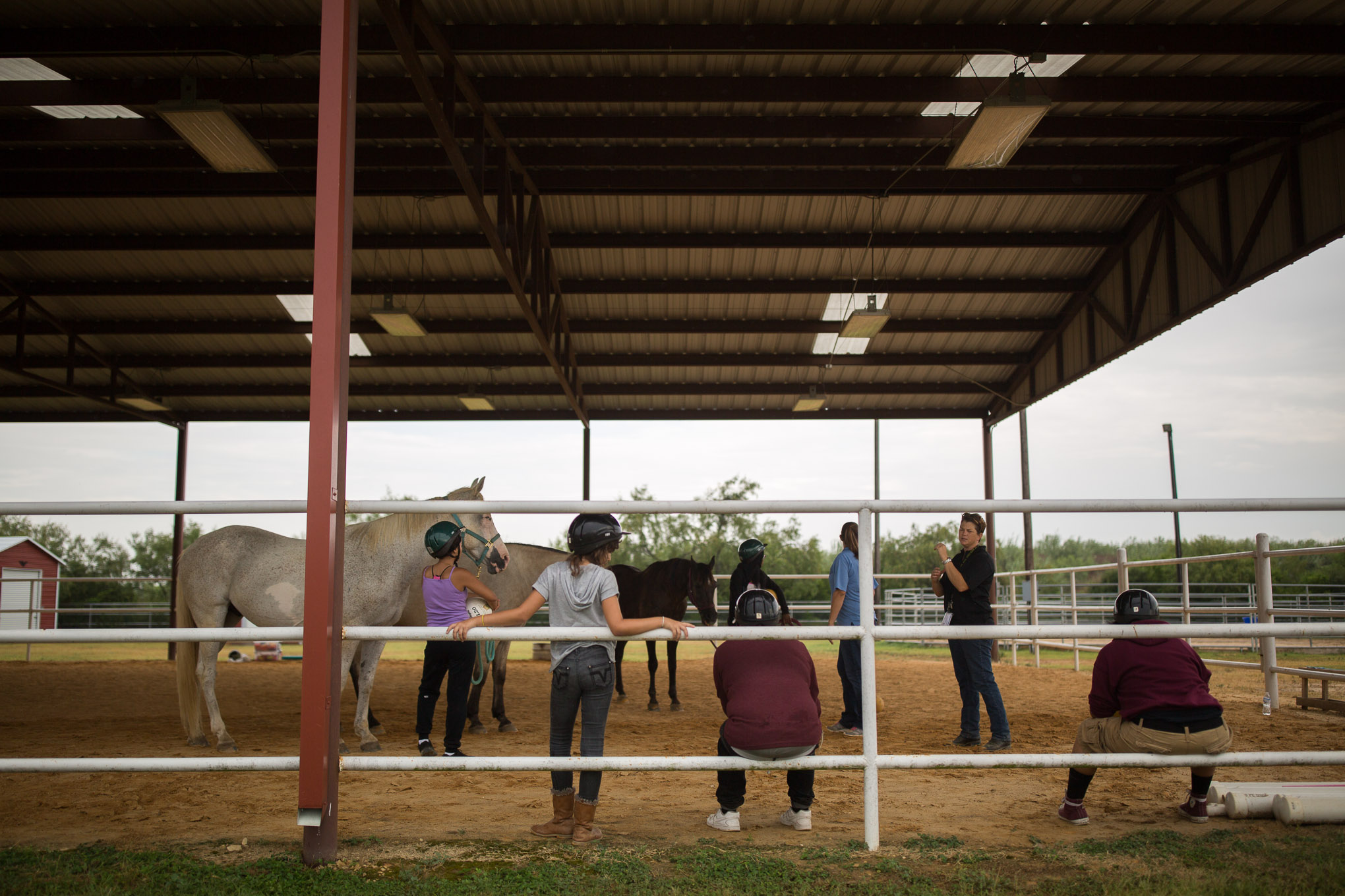Crossroads participants take a break as they receive instruction during equine therapy at Children and Horses Always Produce Success (CHAPS). Photo by Scott Ball.